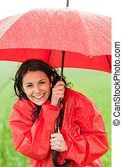 Wet young girl enjoying rainfall with umbrella