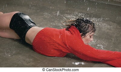 Wet young woman in red sweater and black shorts is dancing on the floor under the rain and splashes of water. Drops water, rain, contemporary dance