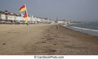 Weymouth beach Dorset UK with flags blowing in the breeze