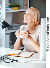 What a beautiful day! Beautiful young woman holding cup with hot drink and looking away with smile while sitting at her working place in office