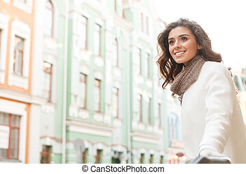 What a great place! Beautiful young women looking away and smiling while standing outdoors