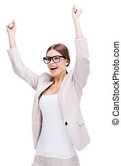 What a lucky day! Happy young businesswoman keeping arms raised while standing against white background