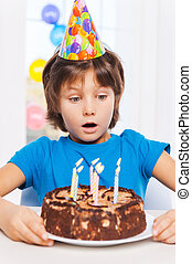 What a surprise! Surprised little boy looking at the birthday cake and preparing to blow the candles