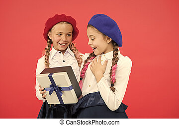 What a wonderful surprise. Happy children with small gift box wrapped with ribbon bow. Little girl giving present to friend. Small kids enjoying holiday celebration. Birthday surprise. Happy birthday