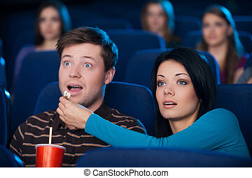 What an exciting movie! Excited young couple eating popcorn and drinking soda while watching movie at the cinema