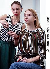 Pleasant professional visagiste standing near her client - ...
