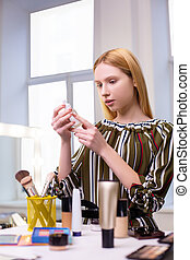 Attractive nice woman looking at the bottle with lotion - ...