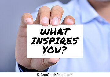 WHAT INSPIRES YOU? message on the card shown by a man