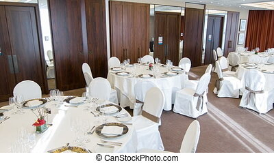 Go to banquet. Beautiful interior of luxurious and famous restaurant with covered white tables refined plates and glasses prepared for happy celebration of different kinds of holidays