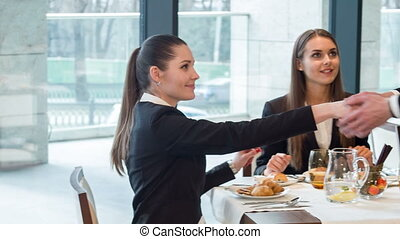 Work with lunch. Nice dark-haired young women sitting at table in some restaurant having lunch and meeting handsome smiling businessman giving talk about job