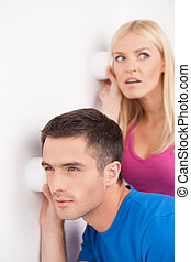 What is going on out there? Beautiful young couple eavesdropping near the wall using tea cups