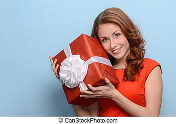 What is inside this box? Attractive young woman holding a gift box in her hands standing against blue background