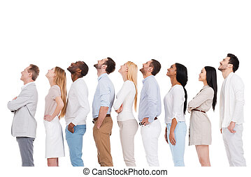 What is that? Side view of positive diverse group of people in smart casual wear looking up while standing in a row and against white background