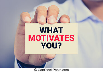 WHAT MOTIVATES YOU? message on the card held by a man hand