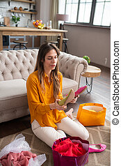 Long-haired girl in a mustard color blouse holding shoes and looking thoughtful