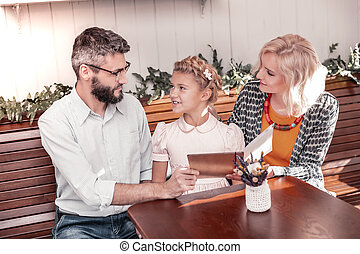 Nice pleasant family reading the menu together