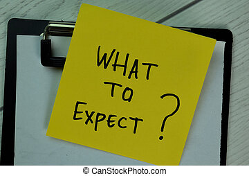 What to Expect? write on sticky notes isolated on Wooden Table.