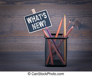 What's New. A small blackboard chalk and colored pencil on wood background