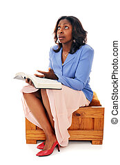 A woman with an opened Bible, looking heavenward with a questionig look. Isolated on white.