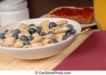 Wheat cereal with blueberries, toast and orange juice