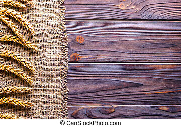 Wheat ears border on old burlap background