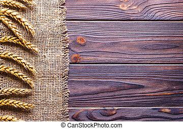 Wheat ears border on old burlap background