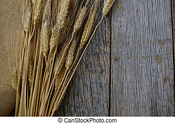 Wheat Ears on Burlap and Wood Background