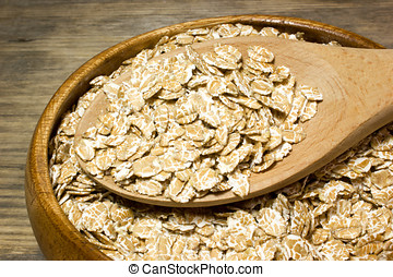 Wheat flakes in wooden spoon on wooden background