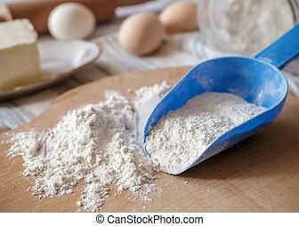 Wheat flour in blue plastic spoon on wooden board