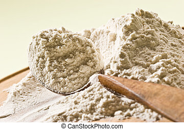 flour - wheat flour on the wooden board with spoon