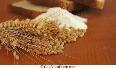 Close up dolly shot of the wheat, grain, flour and bread that goes into baking a loaf of fresh, healthy bread.