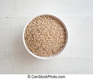 Wheat groats in a bowl on wooden background