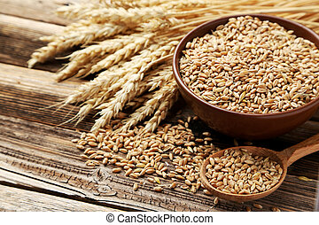 Wheat in bowl on brown wooden background