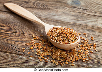Wheat in wooden spoon on old boards