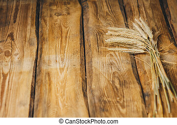 Wheat or rye spikelets on wooden background close up