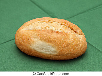 Wheat roll on the green napkin.