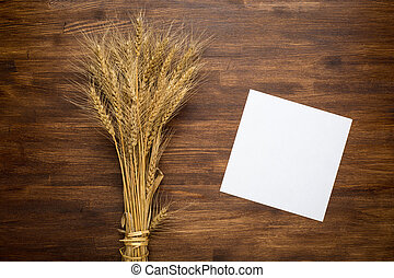 Wheat spikes on dark wooden board with paper