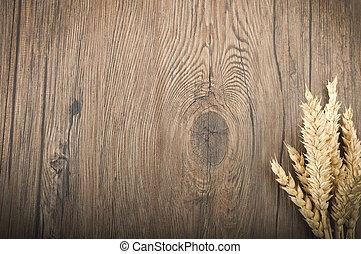 Wheat spikes on the dark wooden board