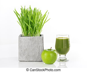 Wheatgrass, apple and a glass of fresh green juice, on white background.