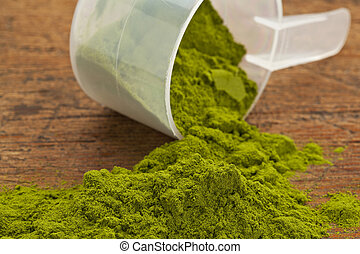 wheatgrass powder spilling of a plastic measuring scoop against grunge wood background