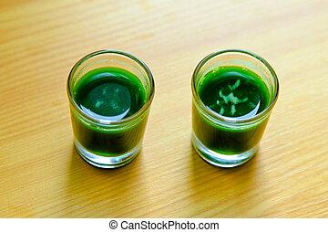 Two shoots of organic wheatgrass green juice