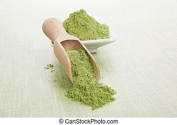 Wheatgrass. - Green superfood. Wheat grass ground on wooden...