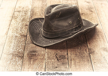 wheathered outback hat on rustic red barn wood, sepia toned ...