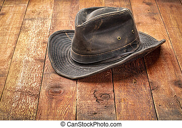 wheathered outback hat on rustic red barn wood