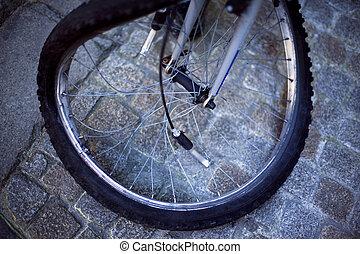 A broken wheel bike on a paved square