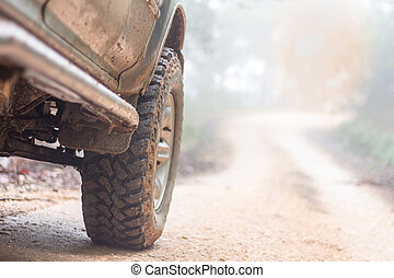 Wheel closeup in a countryside landscape with a muddy road, Off-road travel on mountain road, Adventure Travel, Rainy Season.