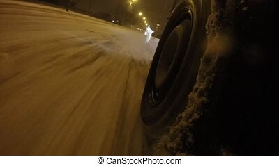 Wheel closeup on snowy roads. The car rides on a...