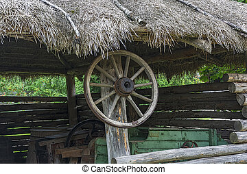 Wheel from the countryside cart hanging on a wooden pole