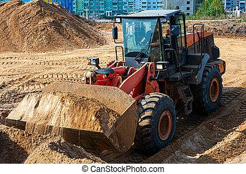 Wheel Loader At Eathmoving Works. Heavy construction machine. Wheel loader transports sand in a sandpit