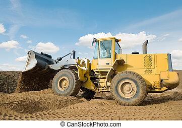 Wheel loader machine unloading sand at eathmoving works in construction site